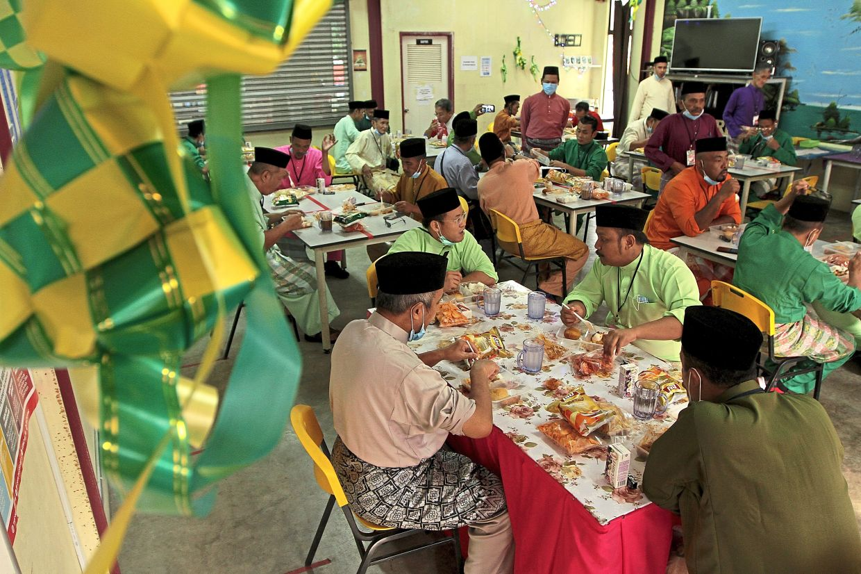 Some of the residents of the Homeless Transit Centre at Jalan Pahang having a Raya meal while observing social distancing.