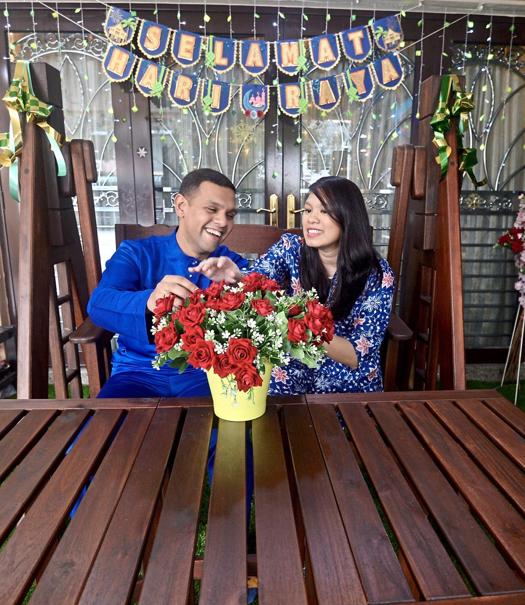 Abdul Rahman and Elya sitting in their festively done-up house porch.