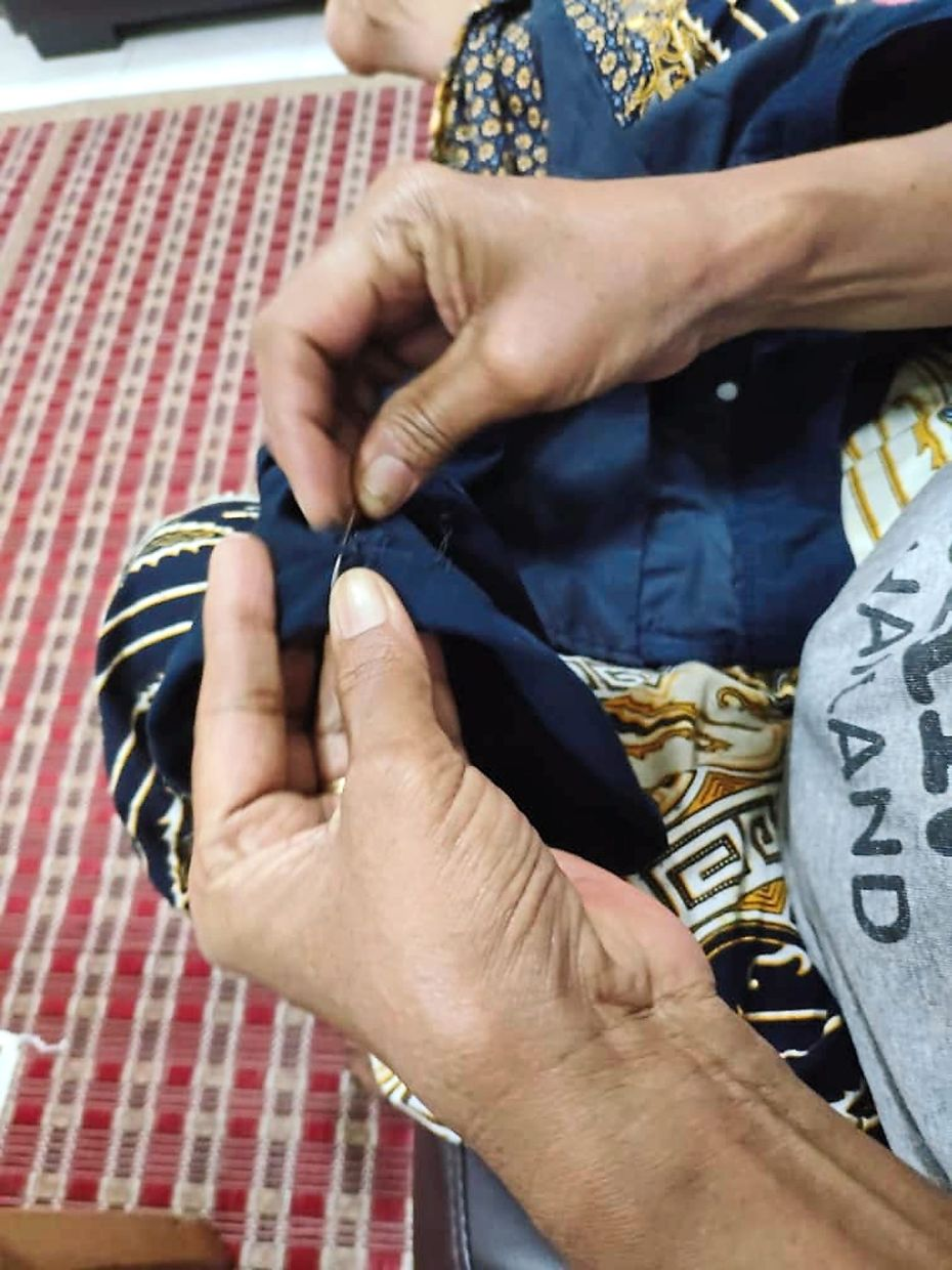 Jeeva carefully sewing neat stitches on the shorts.