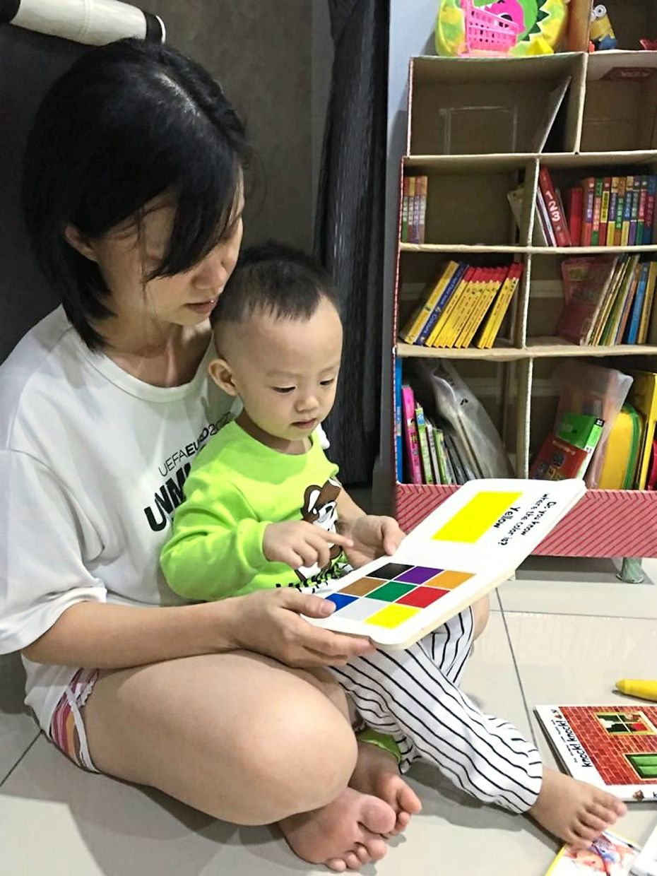 Yap reading to her son from his collection of books.