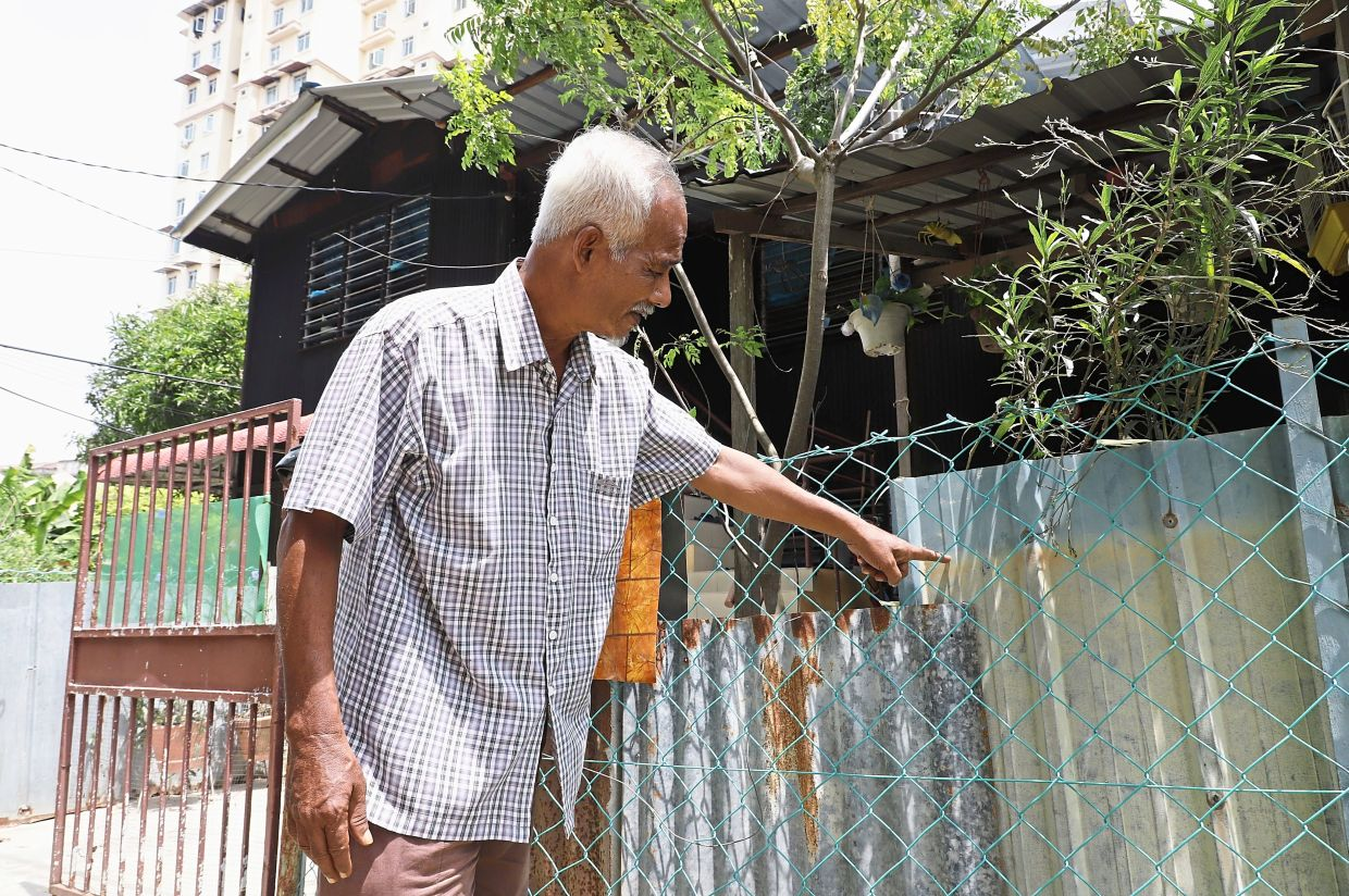 Mazlan showing how high the water rose at his house in Jalan P. ramlee.