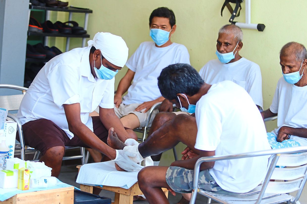 Ravi (left) dressing the wound on a resident's leg at the home.