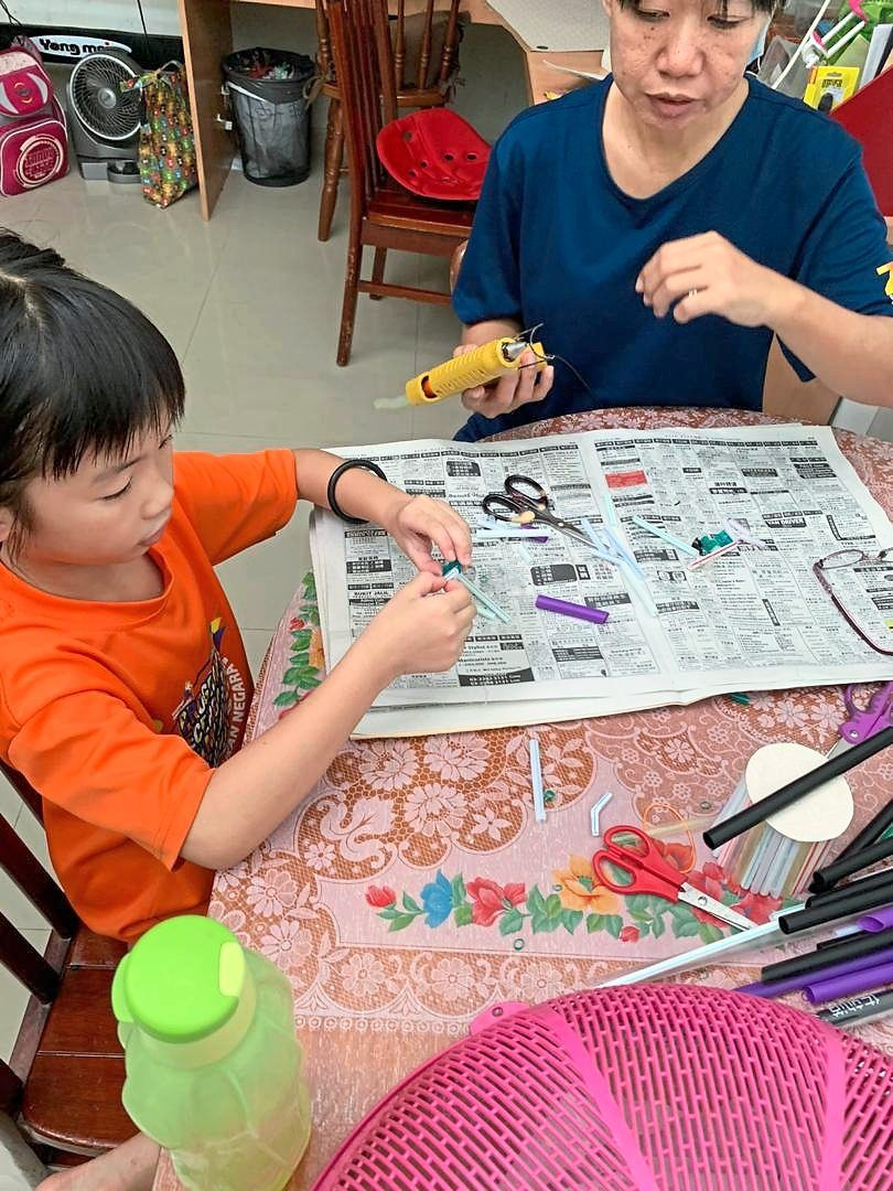 Yong and her daughter creating decorative items using single-use plastics.