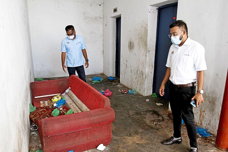 MBSP councillors P. David Marshel (left) and K. Jason Raj showing    furniture  discarded at the Taman Perai Indah apartments in Lorong Perusahaan Baru, Penang. — Photos: CHAN BOON KAI/The Star