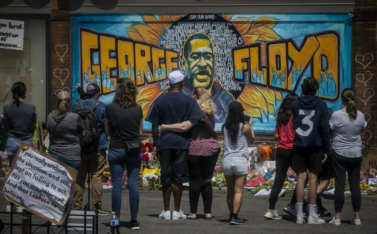 Visitors make silent visits to a memorial featuring a mural of George Floyd, near the spot where he died while in police custody near the intersection of East 38th Street and Chicago Avenue, Minneapolis. The mural was done by a group of local artists. It features Floyd's full name displayed prominently across the wall, the portrait resting in between, and in the backdrop, a sunflower with the names of other individuals who have been killed by police over the years. Photo: AP