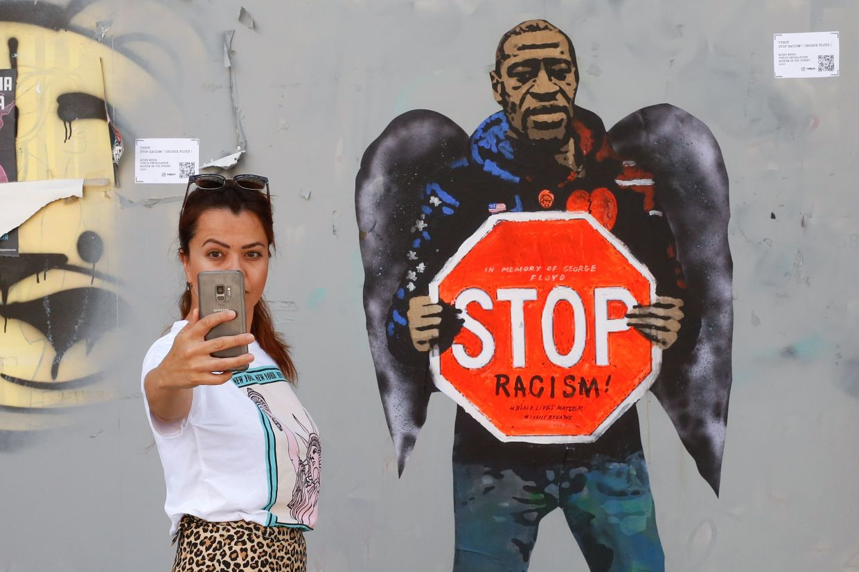 A woman takes a selfie picture posing next to a street mural work by urban artist Salvatore Benintende aka 'TVBoy' depicting George Floyd with angel wings and holding a stop traffic sign against racism, in a street of Barcelona recently. TVBoy, an Italian based in Barcelona, is known for his Urban Pop Art movement works. Photo: AFP