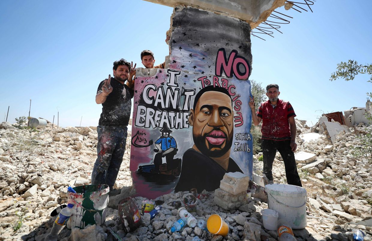 Syrian artists Aziz Asmar (left) and Anis Hamdoun finish a mural depicting Floyd in the town of Binnish in Syria's north western Idlib province on June 1. They used a bombed out house wall in their neighbourhood as their 'canvas'. Photo: AFP