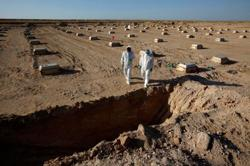 Iraqi militiamen drop guns to dig graves for coronavirus victims