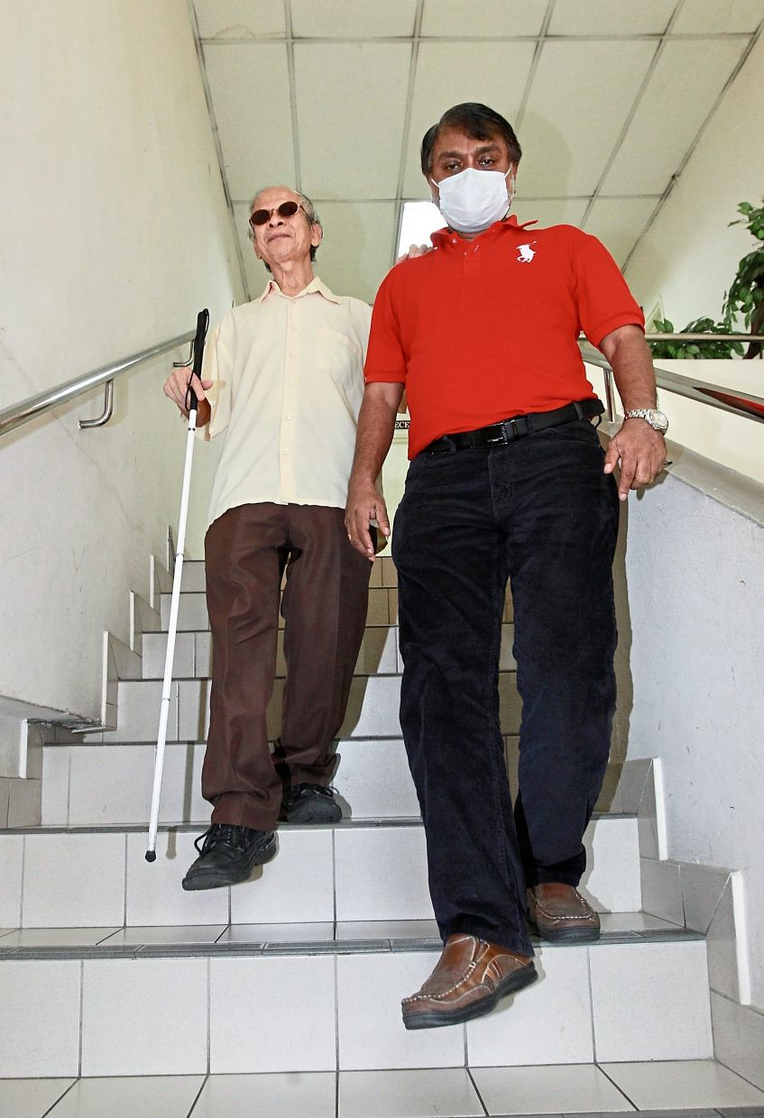 Thomas (right) guiding Ooi down the stairs of the MAB office in Brickfields.