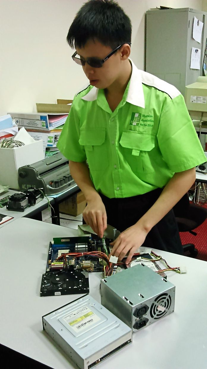 A visually-impaired student learning to repair a computer at one of MAB's training centres.