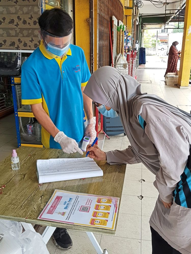Being responsible: This shop in Jalan Teluk Pulai, Klang, which sells household items, gives customers the option to either scan a QR code or write down their details. — EDWARD RAJENDRA/The Star