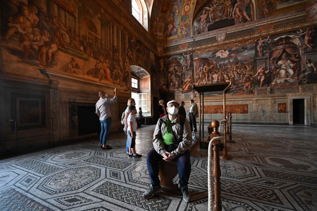 Visitors enjoying quiet time in one of Raphael's Rooms in the Vatican Museums. For locals, this is the best time to visit the Vatican Museums, which are usually inaccessible because of the huge crowds of tourists. Photo: AFP
