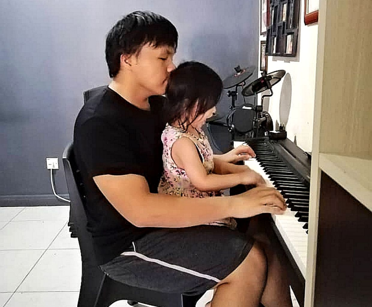 Zechery with his little sister, playing the piano at home during the MCO/CMCO. Photo: Elmus Zechery