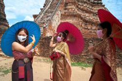 Thais return to temples – in masks