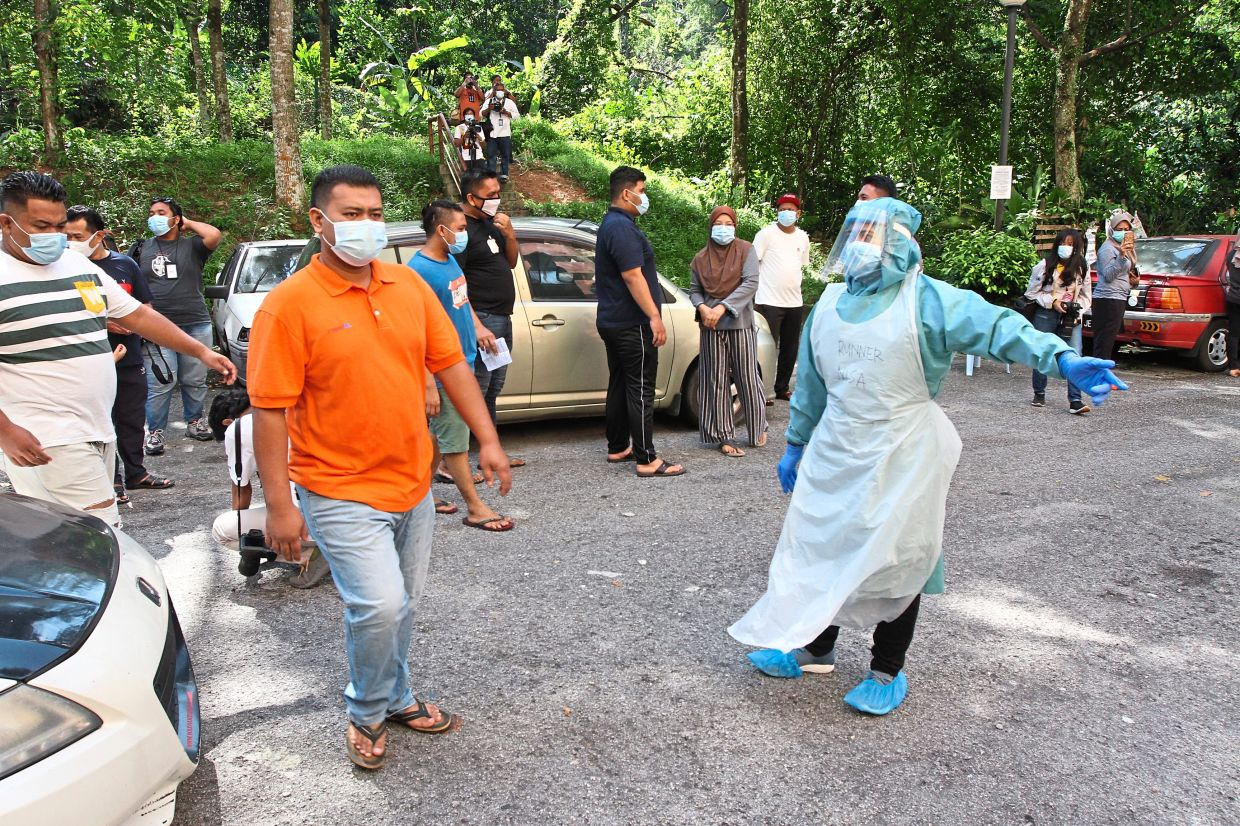 Health Ministry personnel showing residents where to go for the Covid-19 mass testing at Pangsapuri Segar Ria in Cheras.
