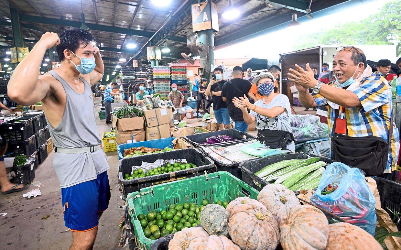 Bravo: Chin flexing his muscles to the admiration of traders at Pasar Borong Kuala Lumpur.