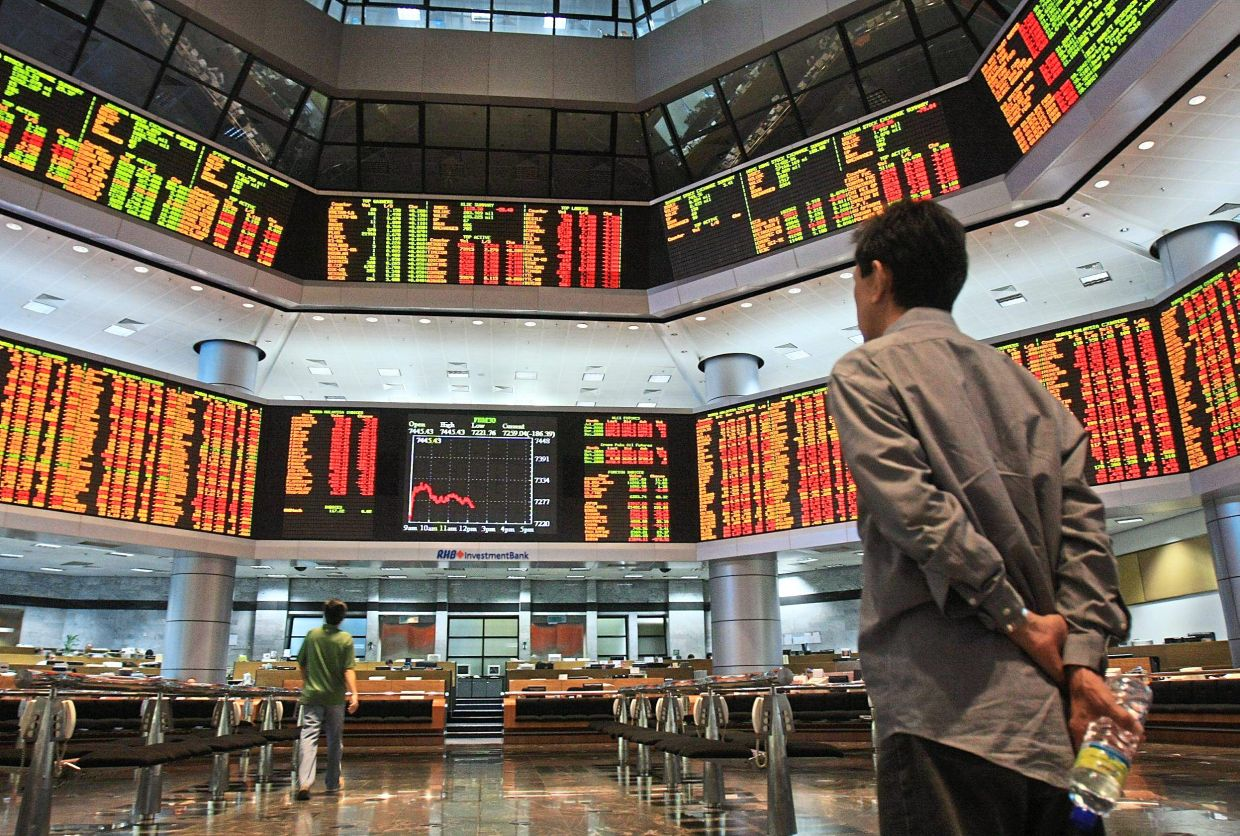 Rallying: Trading in Bursa Malaysia counters at a local bank. The FBM KLCI could peak above 1,600 points in the short term.