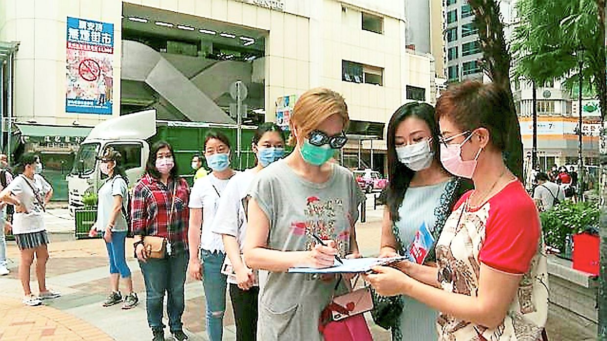People's support: Residents line up to sign a petition supporting the national security legislation for Hong Kong. Hong Kong's violent riot scene may be a thing of the past once the security law is implemented. — China Daily