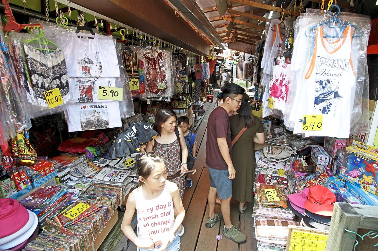 Brisk business: Tourists browsing souvenir stalls at the Chew Jetty in George Town in this 2019 file photo.