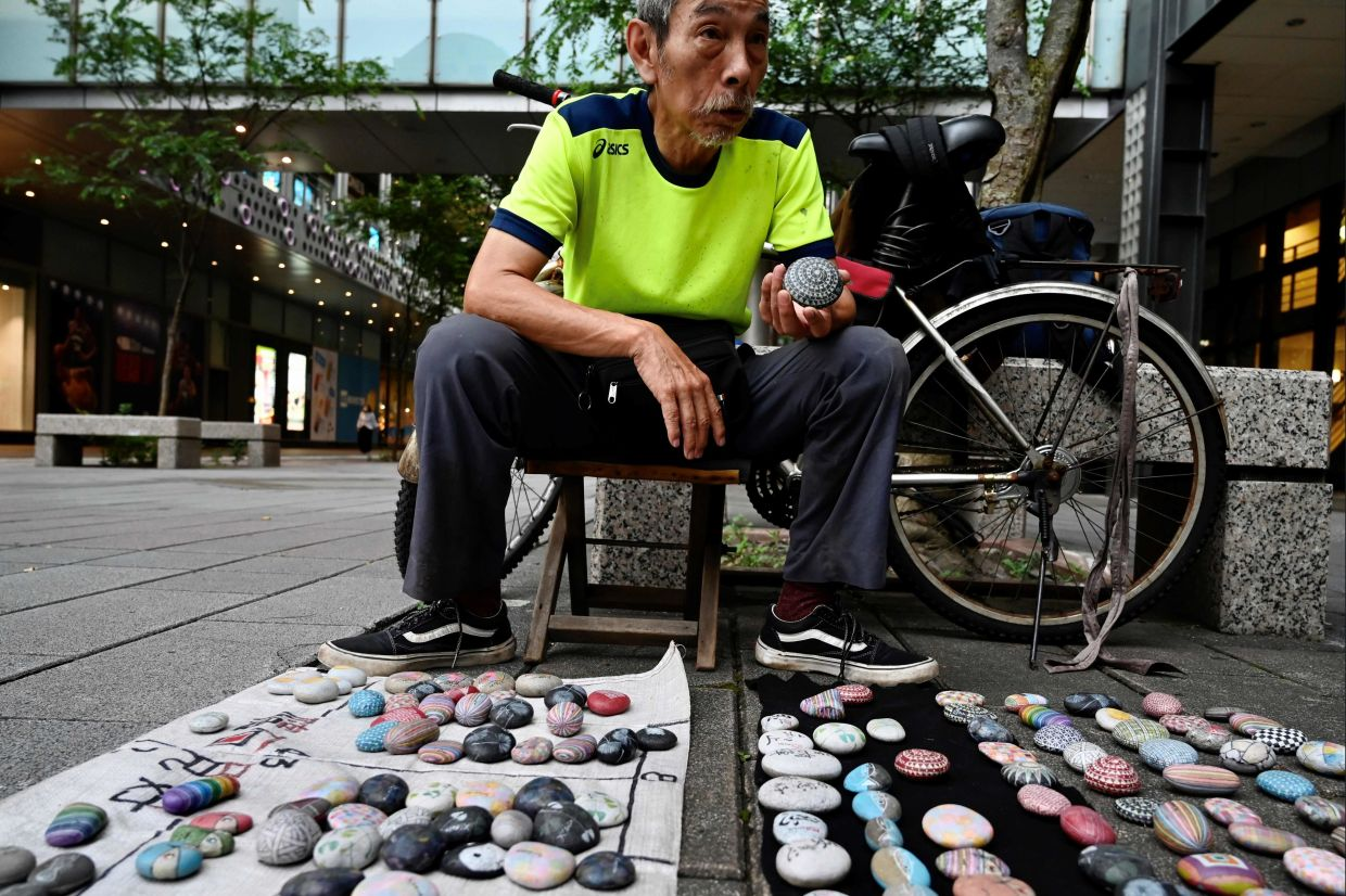 Artist Wu Rong-bi, also as know as 'Uncle Stone', displaying colourfully painted stones along a street in Taipei. Photo: AFP