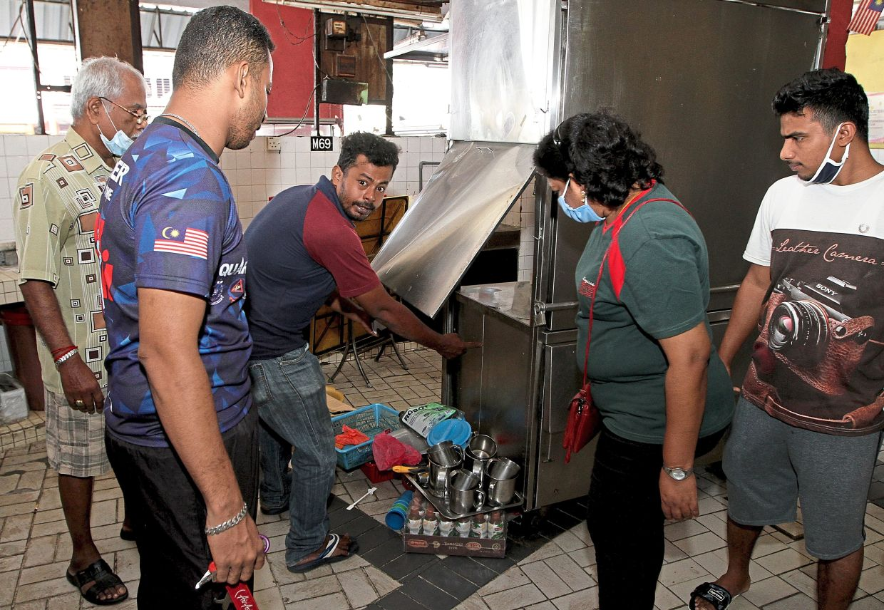 Jamil (centre) showing how thieves prised open his stall's storage compartment at the Pasar Besar Jalan Othman in Petaling Jaya.