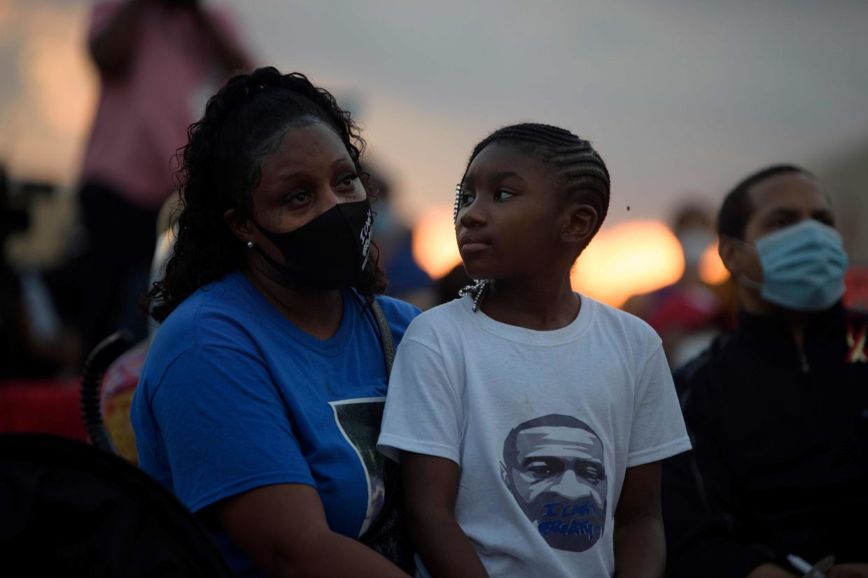 A woman and a young girl attend a candlelight vigil for George Floyd at Jack Yates High School in Houston.