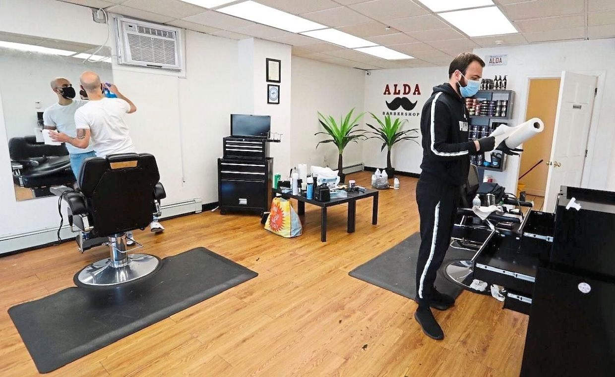 Elias Chalita and Hasan Halila preparing to open Alda barbershop in Quincy, Massachusetts, last Monday, by appointment only.