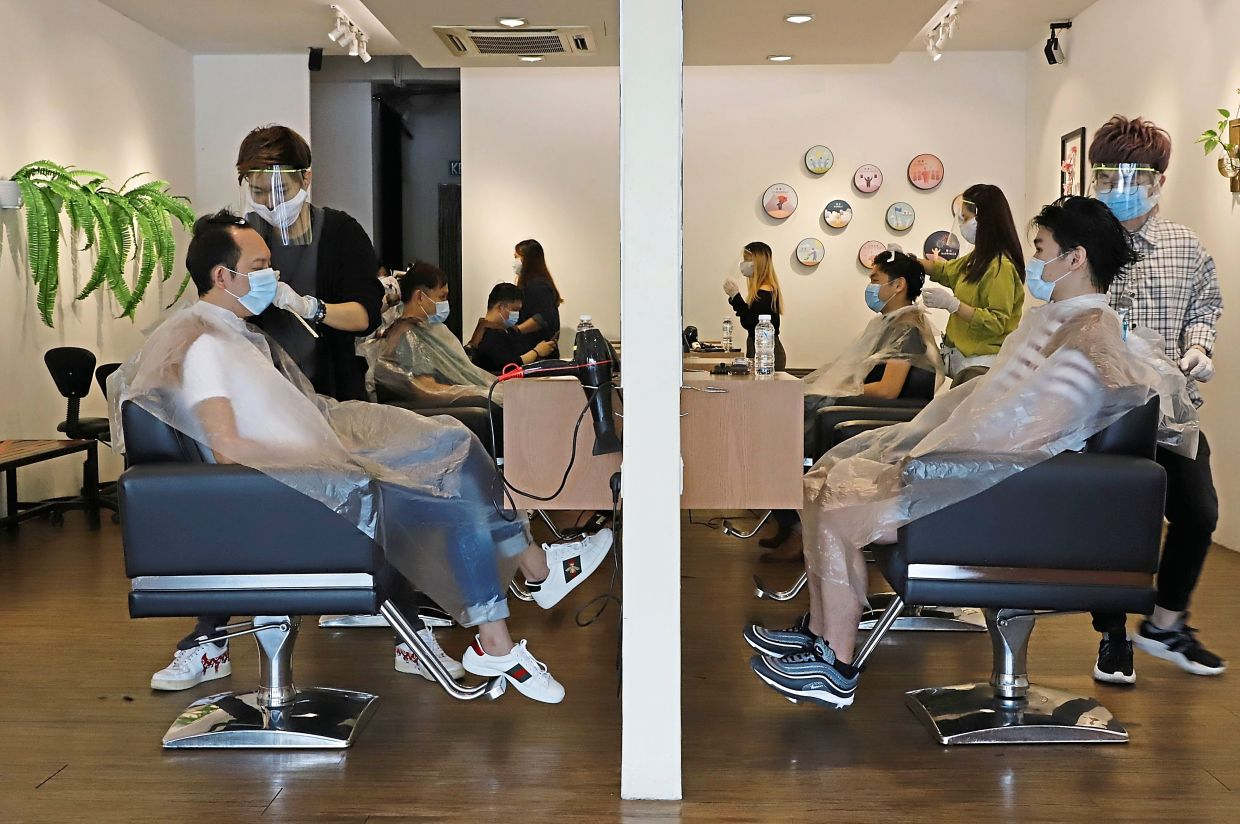 Customers getting their haircut and styling at a hair salon in Bayan Lepas.