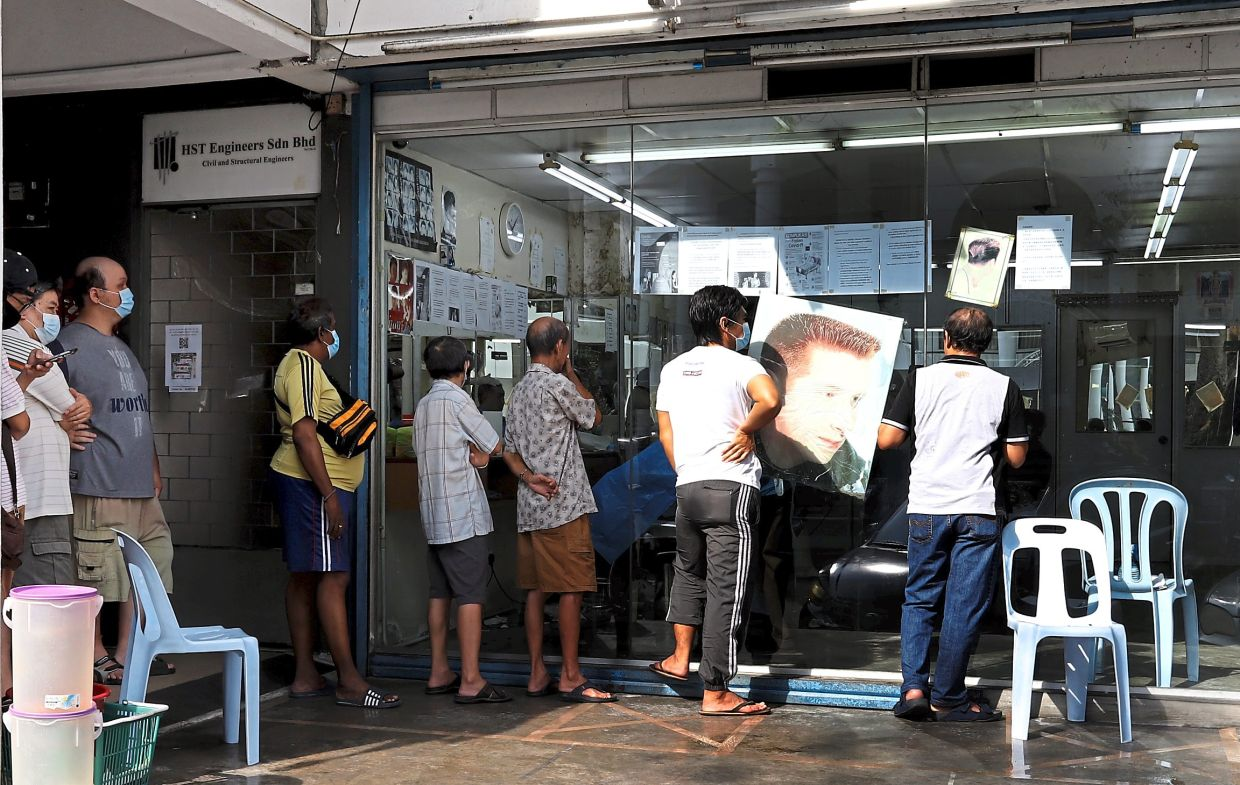 A long queue of  customers waiting  for their haircut  outside a barber shop in Ayer Itam, Penang.  — Photos: LIM BENG TATT/The Star