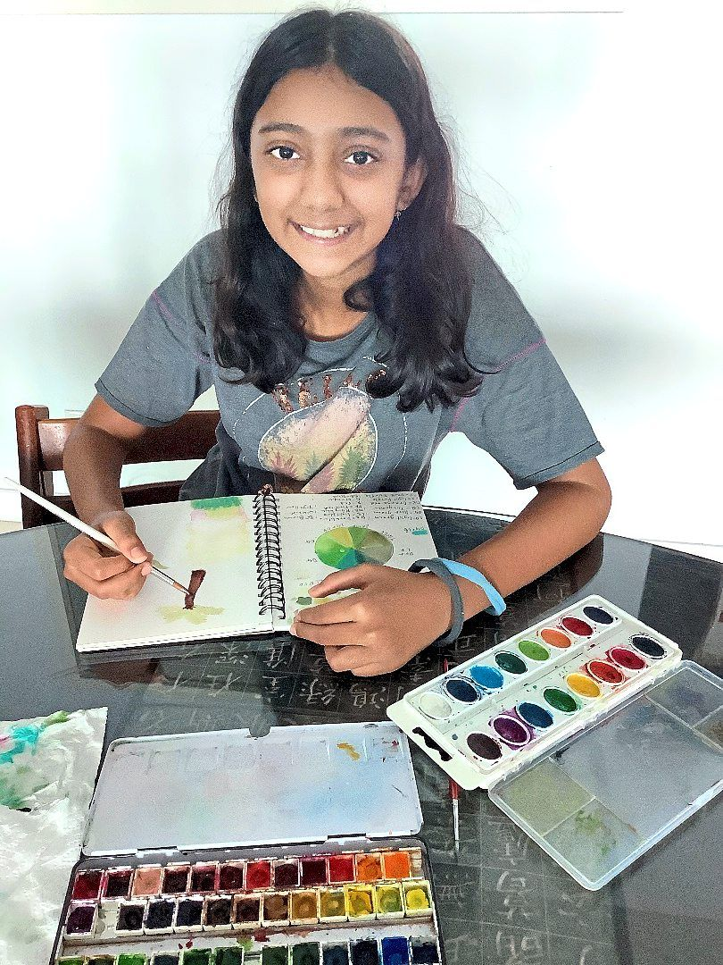 Apsara puts her artistic talent to good use by making watercolour bookmarks to sell at the fair. Photo: Apsara Karim