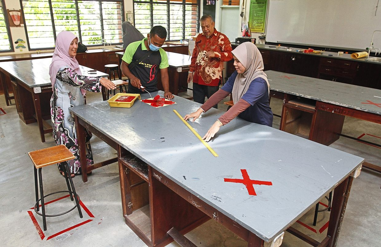 Azrina (left) instructing lab technicians Mohd Anas Syamsul (second left) and Rahimah Md Rejab (right) to    properly measure the seating position at the school lab. With them is senior assistant (co-curriculum) Mustafa Hashim. — Photos: ZHAFARAN NASIB/The Star