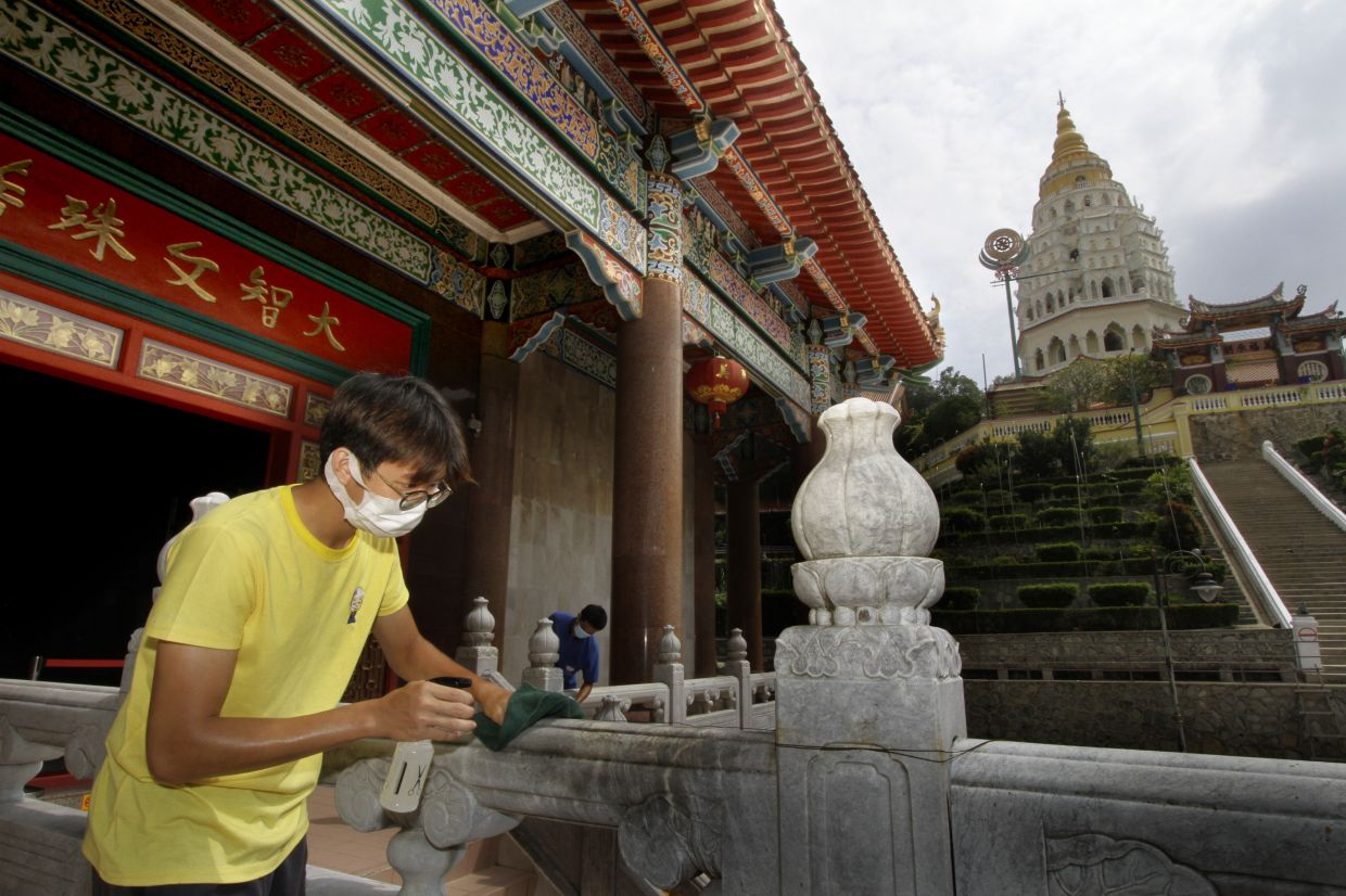 Temple staff wipes down hand railings with cleaning solution at the Kek Lok Si Temple, Penang. As temples and gurdwaras across the country will start reopening this weekend while churches have applied to resume services. CHAN BOON KAI / The Star