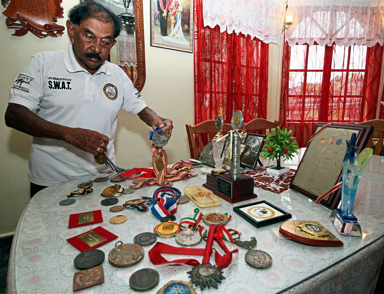 Victor showing the medals and trophies he won throughout his 65-year athletic career.