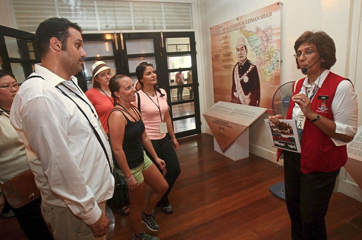 Jane (right) explaining to tourists about the history of Kelab Sultan Sulaiman gallery during the Jalan Jalan @ Kampung Bharu 'Cultural Guided Walk'. — Filepic