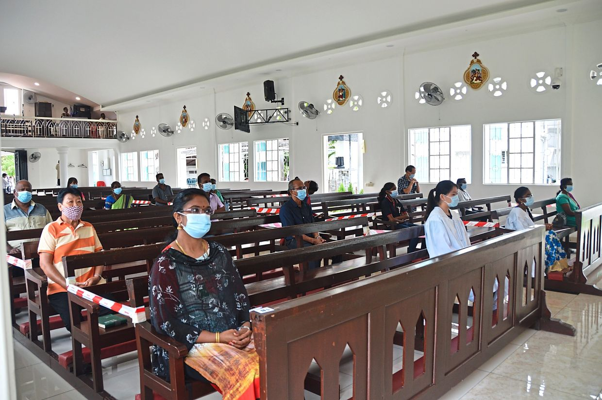 Time to congregate safely: Parishioners observing mass at church after it was reopened. — SARBAN SINGH/The Star