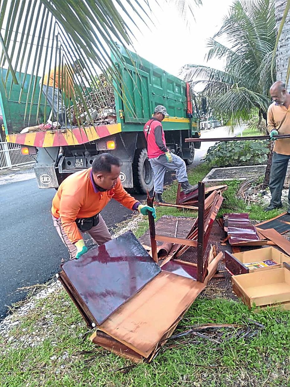 Ipoh City Council workers clearing up illegal dumpsites within the city.