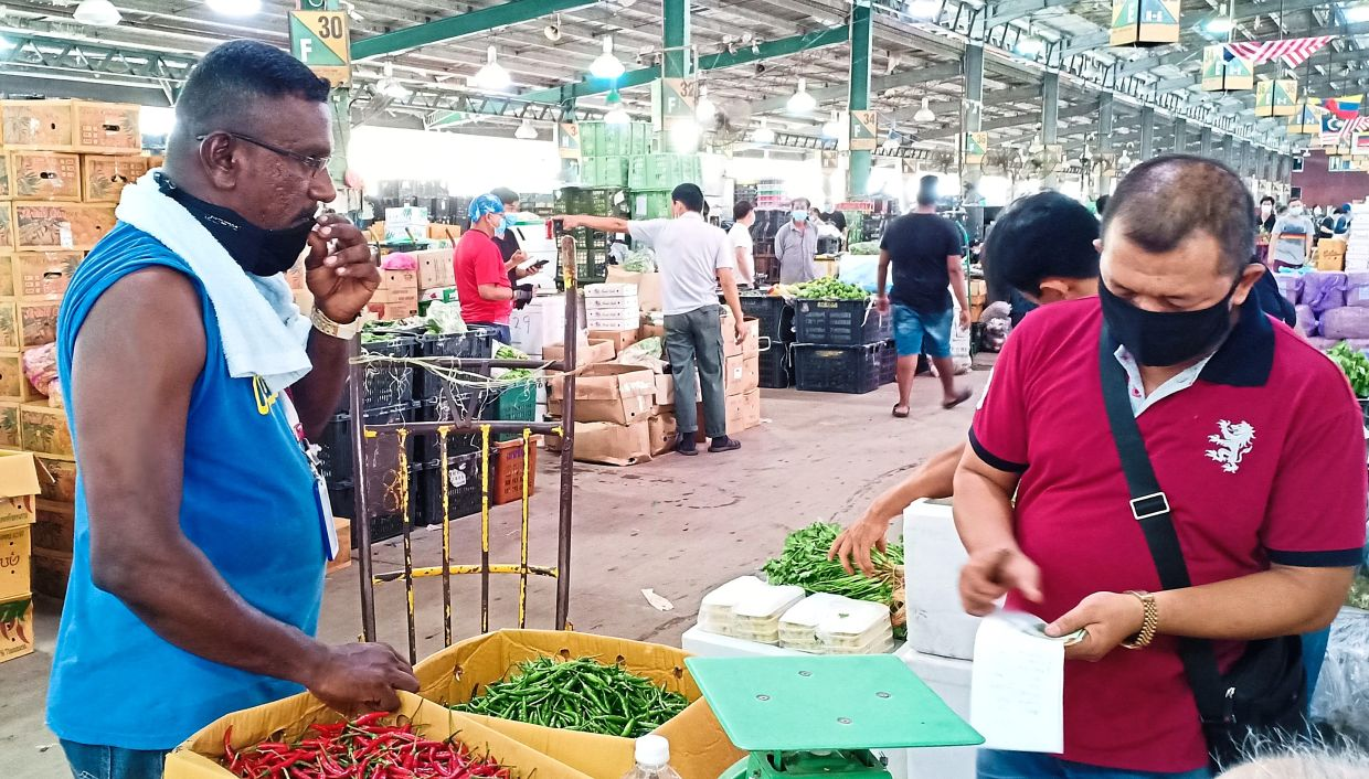 Kumaran (left) quit his previous job and took up work at the market when his former employer cut his salary by almost half.