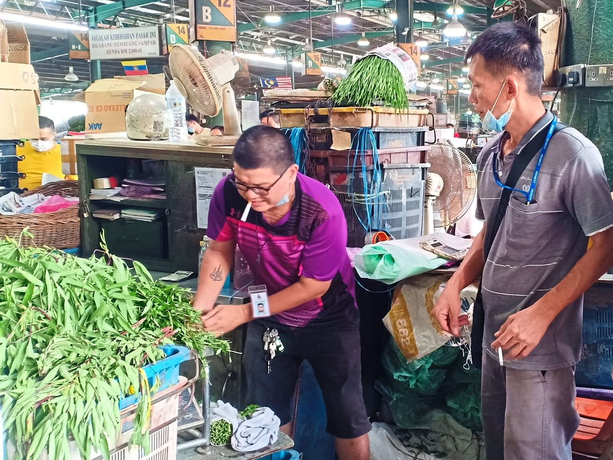Mau (left), a former IT system designer, now moves boxes of fresh produce at the market daily to earn an income for his family.