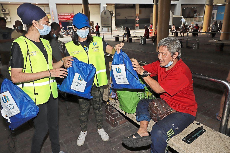 Volunteers from United Sikhs presenting goodies at the Komtar bus terminal.