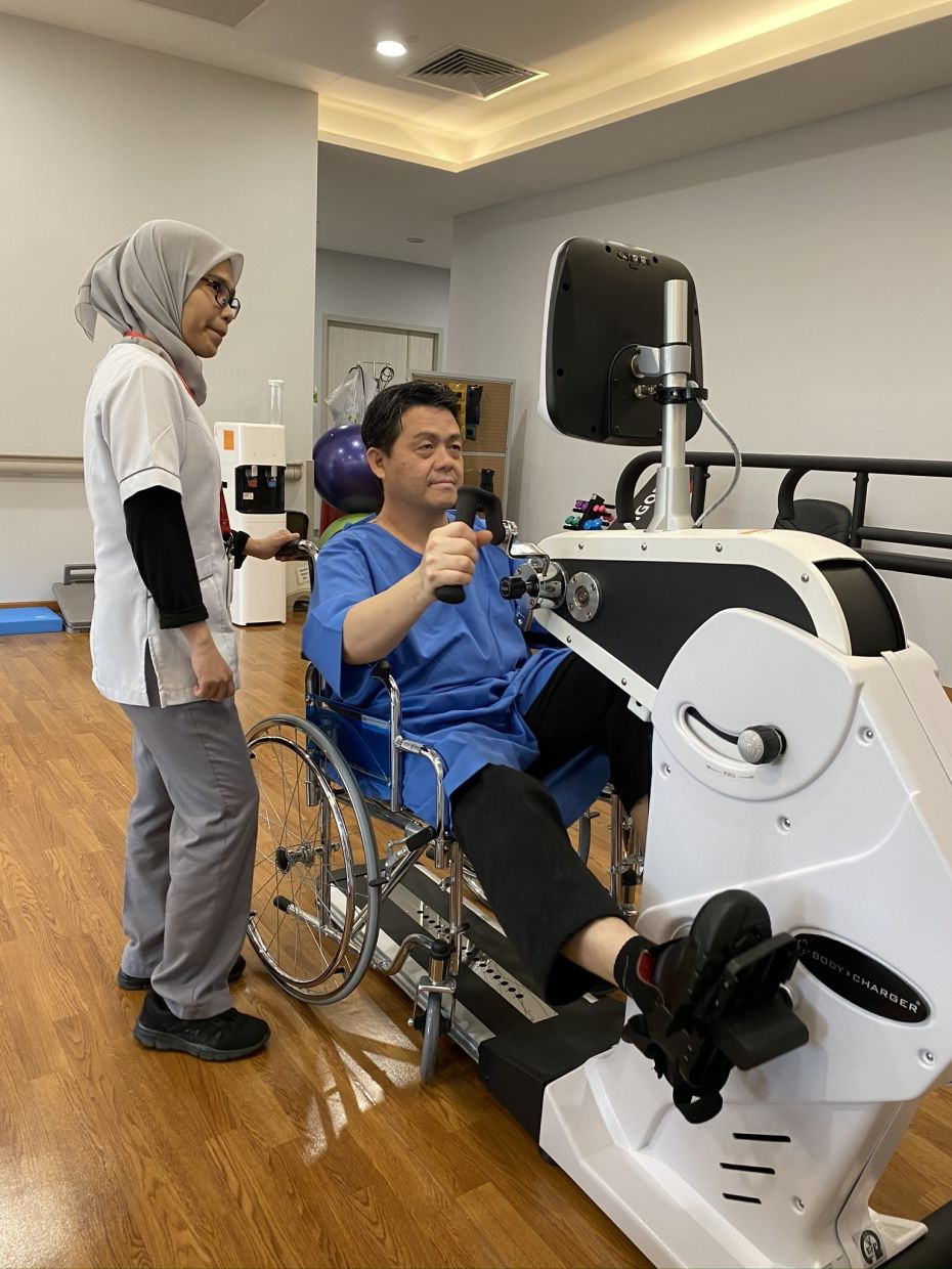 A stroke patient exercises his muscles with the help of a machine, supervised by a physiotherapist.