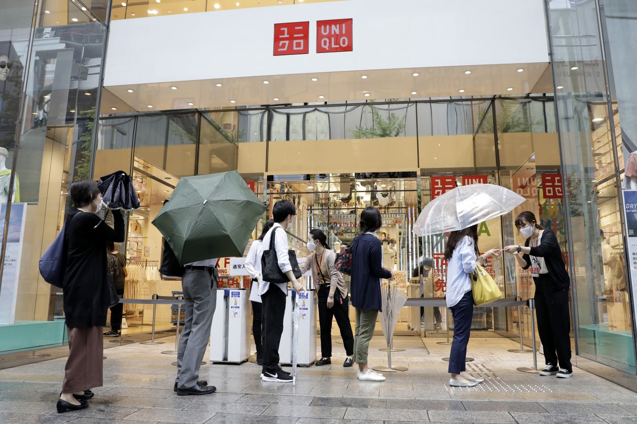 Customers collecting queue tickets to purchase Uniqlo AIRism masks at a Uniqlo store, in Tokyo, Japan, on Friday, June 19, 2020. — Bloomberg