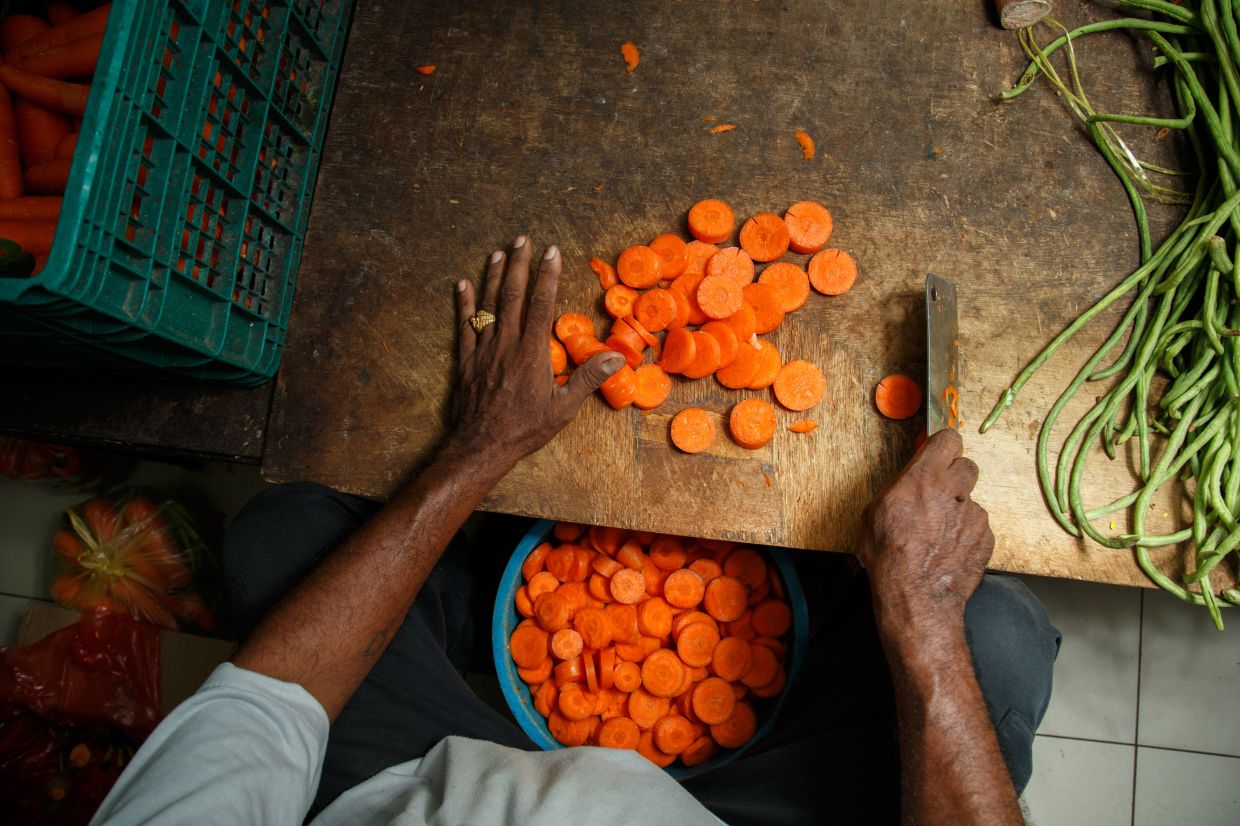 Taiping Zoo staff cutting up carrots for the animals. MCO or not, the animals had to be fed daily so staff continued going in to work even before the recovery MCO period. — Filepic/The Star