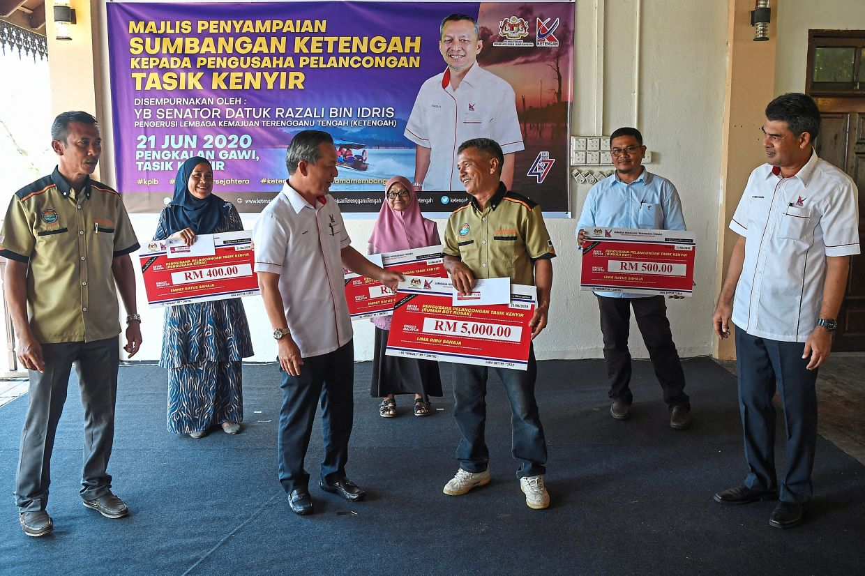 Razali (third from left) with some of the tourism operators after presenting the contributions. Looking on is Ketengah general manager Tengku Ahmad Nazdri Tengku Musa (right). — Bernama