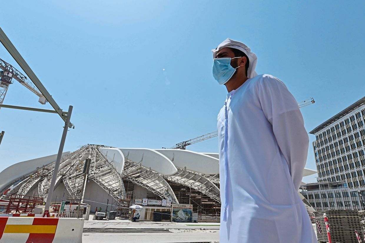 An Emirati man stands outsite the Dubai Expo 2020 site. Organisers grappling with the complexities of rescheduling the event are intent on delivering the main buildings of the Expo by the original start date.