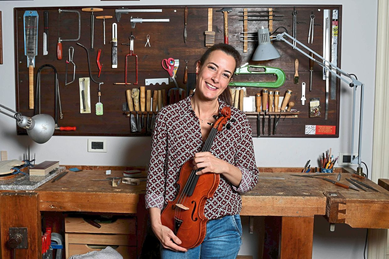 French luthier Friedmann poses with a violin at her workshop.