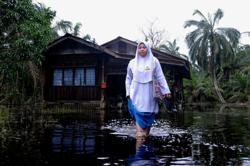 Batu Pahat student wades through flood water to school