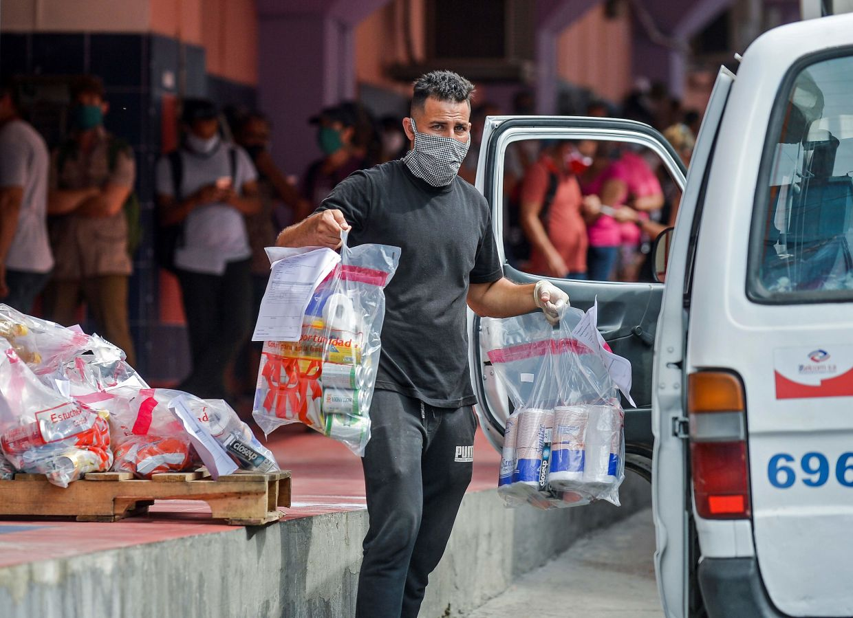 A worker loads online purchases on a van to be delivered, outside a pick up centre in Havana, on June 17. — Yamil Lage/AFP