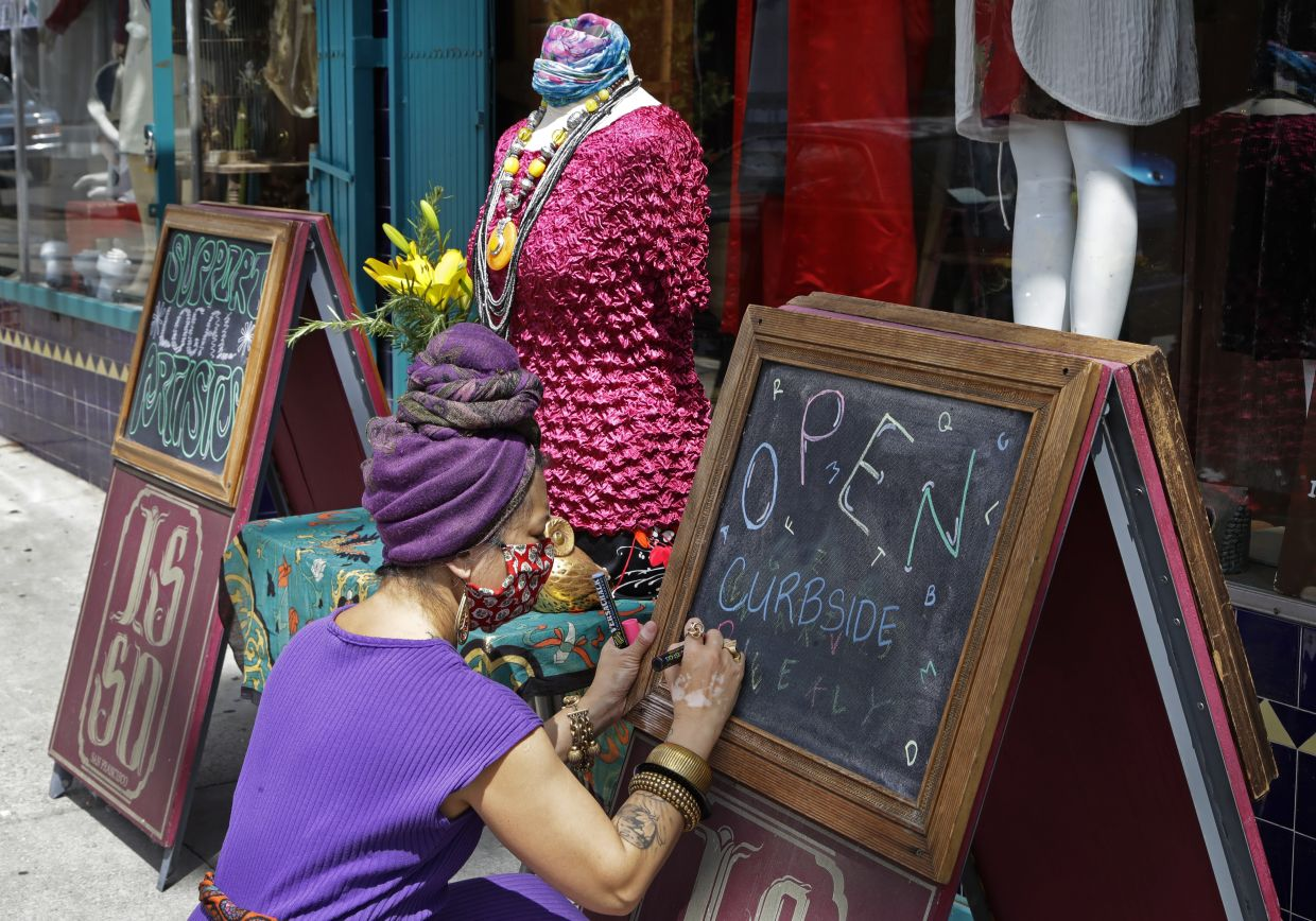 A boutique owner finishes writing a sign in San Francisco. Photo: AP