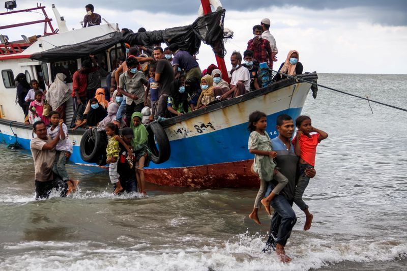 Locals evacuate Rohingya refugees from a boat at a coast of North Aceh Indonesia June 25 2020 in this photo taken by Antara Foto.  Antara FotoRahmad via REUTERS