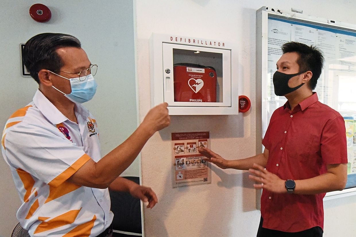 Cheen (left) and Ang showing the AED installed at the apartment.